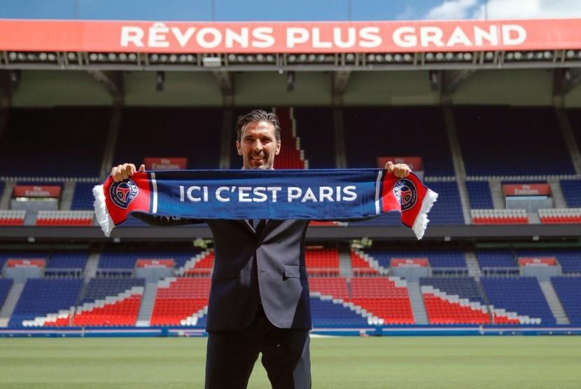Gianluigi Buffon memegang syal tim barunya, Paris Saint-Germain.