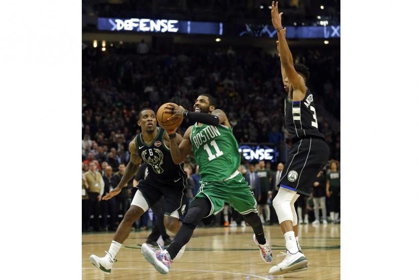 Guard Boston Celtics Kyrie Irving membawa bola.