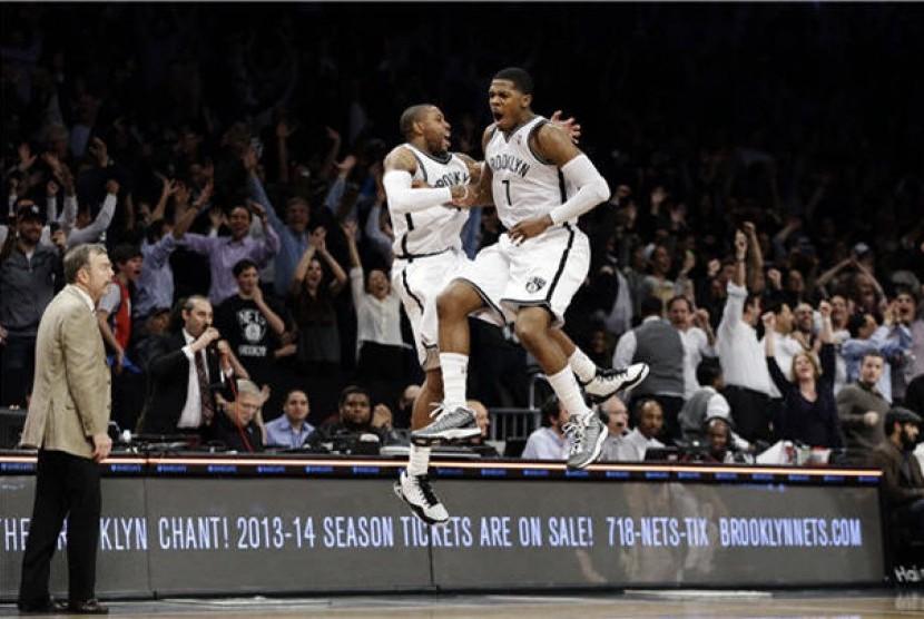Guard Brooklyn Nets, Joe Johnson (kanan), bersama rekannya guards C.J. Watson meloncat gembir setelah tembakannya di detik terakhir membawa Nets menang tipis 113-111 dari Milwaukee Bucks pada laga NBA di Barclays Center, New York, Selasa (19/2).