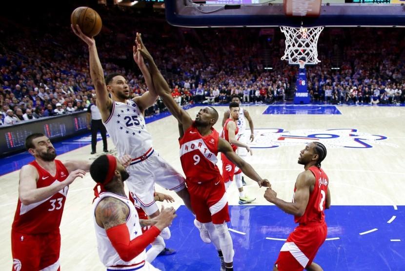 Guard Philadelphia 76ers Ben Simmons melepaskan tembakan dijaga forward Toronto Raptors Serge Ibaka pada gim keenam play-off babak kedua NBA di Philadelphia, Jumat (10/5) WIB.