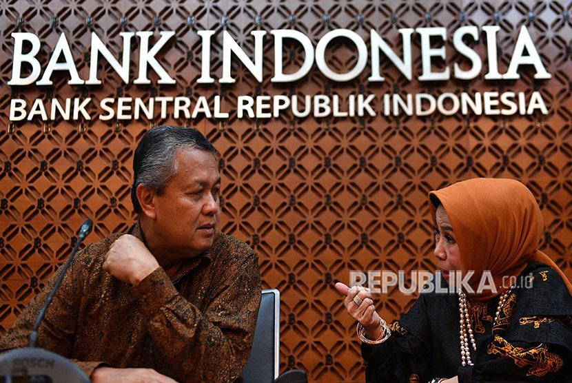 Gubernur Bank Indonesia (BI) Perry Warjiyo (kiri) berbincang dengan Deputi Gubernur Rosmaya Hadi saat memberikan keterangan pers di kantor pusat BI, Jakarta, Jumat (8/6).