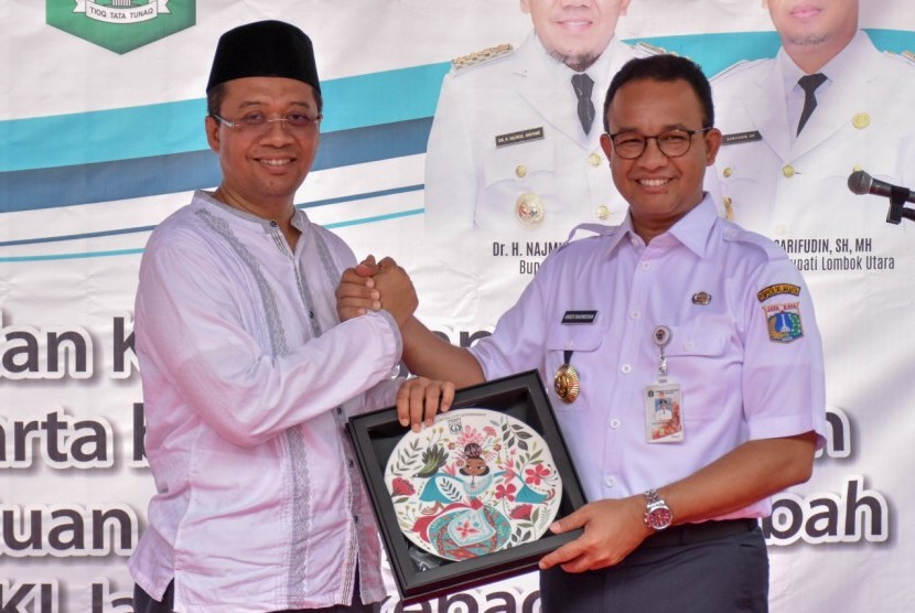 Gubernur DKI Jakarta Anies Baswedan bersama Gubernur NTB Zulkieflimansyah dalam penyerahan bantuan dari Pemprov DKI Jakarta di Lombok Utara, NTB, Jumat (4/1).