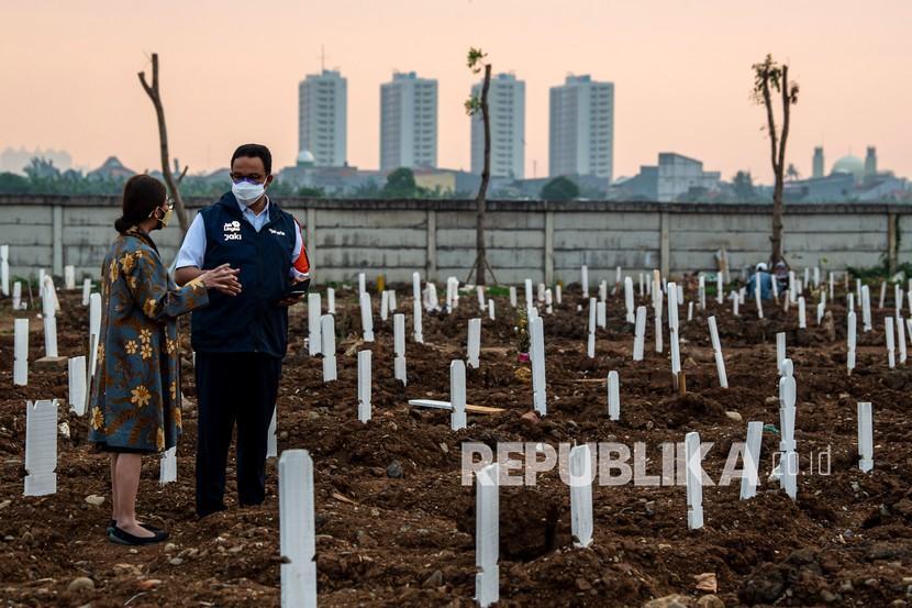 Gubernur DKI Jakarta Anies Baswedan (kanan) berbincang dengan Kepala Dinas Pertamanan dan Hutan Kota Provinsi DKI Jakarta, Suzi Marsitawati (kiri) saat meninjau area pemakaman khusus COVID-19 di TPU Rorotan, Cilincing, Jakarta Utara, Kamis (15/7/2021). Anies Baswedan menyampaikan, pihaknya memakamkan jenazah dengan menggunakan protokol COVID-19 hingga mencapai 306 jenazah.