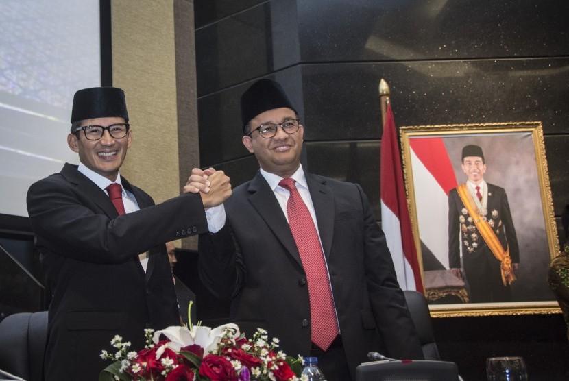 Gubernur DKI Jakarta Anies Baswedan (kanan) berjabat tangan dengan Wakil Gubernur Sandiaga Uno (kiri) seusai mengikuti Rapat Paripurna di DPRD DKI Jakarta