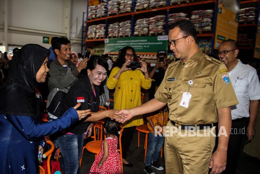 Gubernur DKI Jakarta Anies Baswedan (kedua kanan) menyapa pekerja sebelum membagikan Kartu Pekerja di Jakgrosir, Pasar Induk Kramat Jati, Jakarta, Senin (31/12/2018).