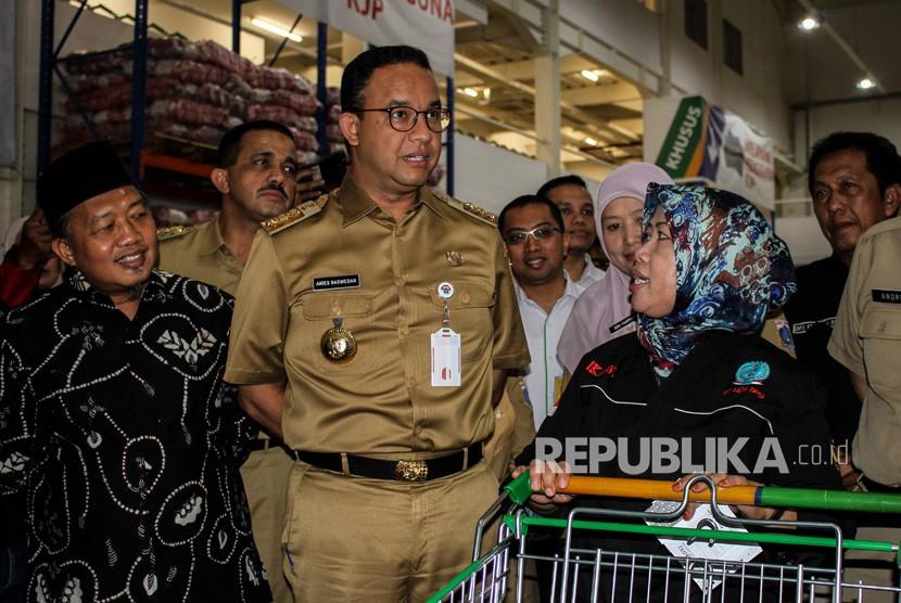 Gubernur DKI Jakarta Anies Baswedan (ketiga kiri) berbincang dengan pekerja setelah pembagian Kartu Pekerja di Jakgrosir, Pasar Induk Kramat Jati, Jakarta, Senin (31/12/2018).