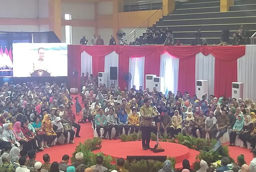 Gubernur DKI Jakarta Anies Baswedan mendampingi Presiden Joko Widodo membagikan sertifikat tanah 16 kelurahan Jakarta Selatan di Gelanggang Remaja Pasar Minggu, Jakarta Selatan, Jumat (22/2).