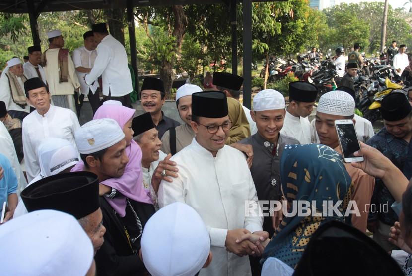 Gubernur DKI Jakarta Anies Baswedan (tengah) bersalaman dengan warga usai menghadiri kegiatan halalbihalal dan doa bersama saat perayaan Idul fitri hari kedua di Makam Wakaf Muslim, Lebak Bulus, Jakarta, Kamis (6/6/2019).