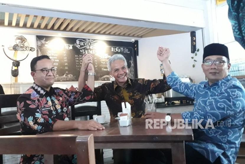 Gubernur DKI Jakarta Anies Rasyid Baswedan (kiri), Gubernur Jawa Tengah Ganjar Pranowo (tengah), dan Gubernur Jawa Barat Ridwan Kamil (kanan), minum kopi bersama di kafe JakBistro Balai Kota DKI Jakarta sebelum pandemi Covid-19.