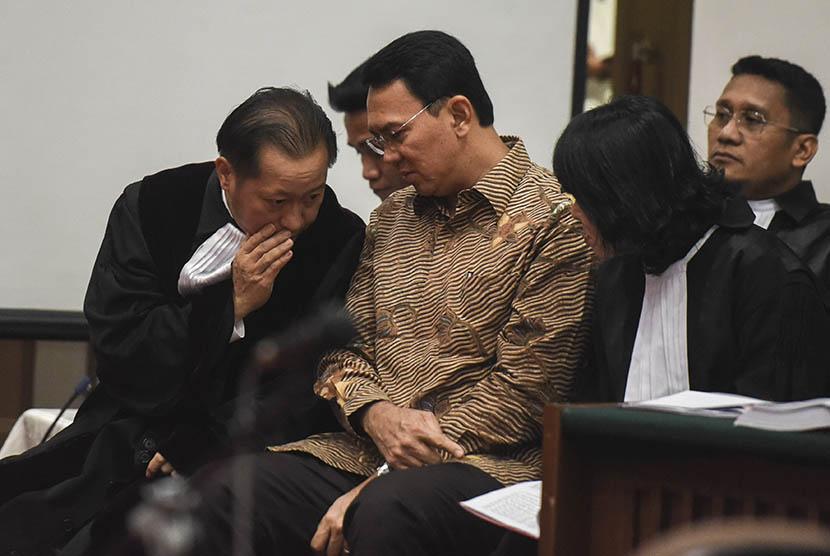 Gubernur DKI Jakarta nonaktif Basuki Tjahaja Purnama alias Ahok (tengah) berbincang dengan penasehat hukumnya saat menjalani sidang lanjutan kasus dugaan penistaan agama di PN Jakarta Utara, Auditorium Kementerian Pertanian, Jakarta, Rabu (29/3).