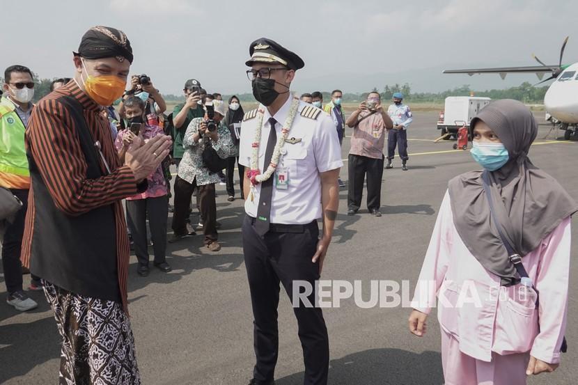 Gubernur Jateng Ganjar Pranowo (kiri), menyambut pilot maskapai penerbangan Citilink yang mendarat dari Surabaya di Bandara Jenderal Besar Soedirman (JBS), Purbalingga, Jawa Tengah, Kamis (3/6/2021). Sebanyak 24 penumpang mendarat dari Surabaya dan 37 penumpang berangkat menuju Jakarta pada penerbangan komersial perdana di Bandara JBS, menandai dimulainya operasional bandara secara komersial.