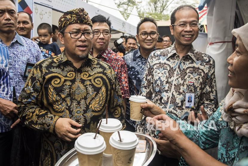 Gubernur Jawa Barat Ahmad Heryawan (kiri) didampingi Direktur Utama Bank BJB Ahmad Irfan (kanan) meninjau stan UMKM binaan saat kegiatan West Java Coffee & Art dan HUT ke-57 Bank BJB di Bandung, Jawa Barat, Jumat (11/5).