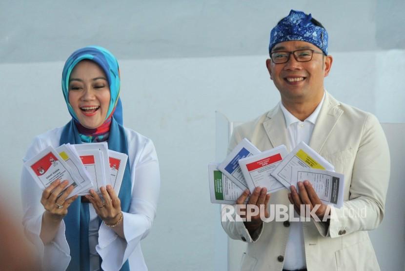 Gubernur Jawa Barat Ridwan Kamil berserta istrinya Atalia Praratya memperlihatkan surat suara usai melakukan pencoblosan Pemilu 2019, di TPS 32, Cigadung, Kota Bandung, Rabu (17/4).