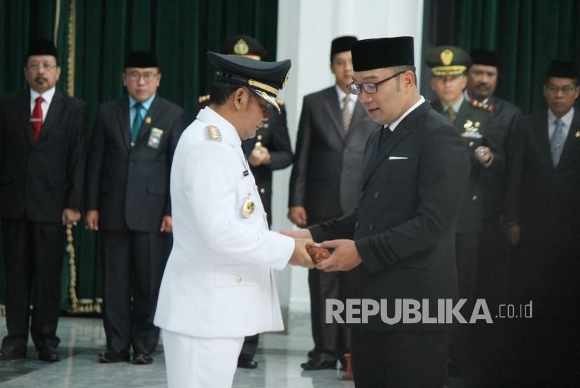 Gubernur Jawa Barat Ridwan Kamil (kanan) melantik Eka Supria Atmaja sebagai Bupati Bekasi definitif yang baru dilantik, di Aula Barat, Gedung Sate, Kota Bandung, Rabu (12/6).