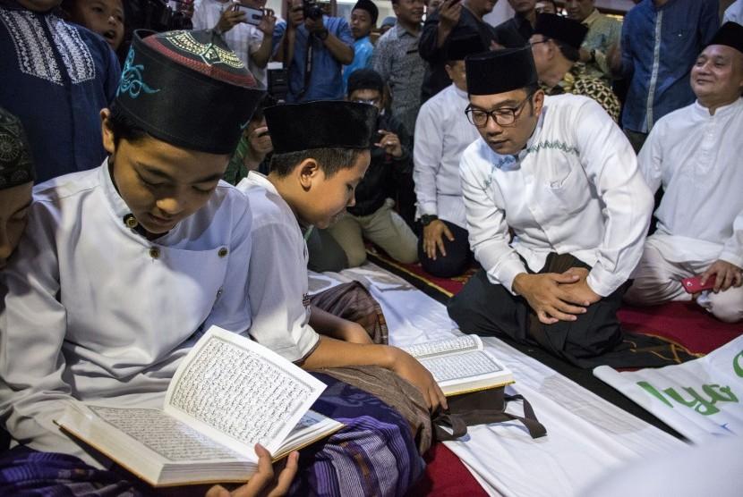 Gubernur Jawa Barat Ridwan Kamil (kedua kanan) melihat anak-anak mengaji saat Launching Maghrib Mengaji di Masjid Agung, Sukabumi, Jawa Barat, Kamis (03/12/2018).