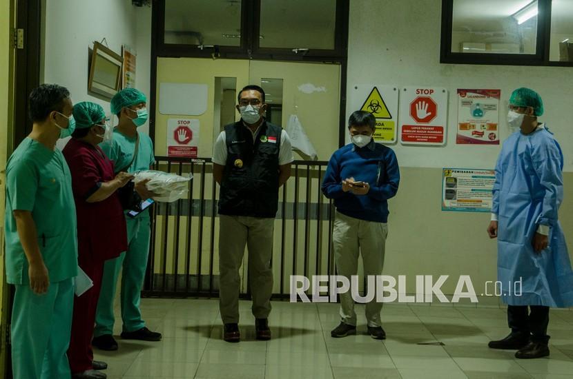 Gubernur Jawa Barat Ridwan Kamil (tengah) didampingi Plt Direktur Pelayanan Medik Keperawatan dan Penunjang Rumah Sakit Dokter Hasan Sadikin (RSHS) Dr.Yana Muhammad Supriatna (kedua kanan) meninjau ruang isolasi Kemuning di RSHS, Bandung, Jawa Barat, Sabtu (12/6/2021). Ridwan Kamil menyatakan tingkat keterisian tempat tidur atau Bed Occupancy Rate (BOR) di keseluruhan Jawa Barat masih dalam tahap terkendali meski mengalami peningkatan mencapai 68 persen dampak arus mudik dan libur lebaran.