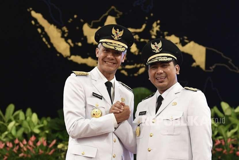 Gubernur Jawa Tengah Ganjar Pranowo (kiri) bersama Wakil Gubernur Taj Yasin Maimoen (kanan) melakukan salam komando usai pelantikan di Istana Negara, Jakarta, Rabu (5/9).