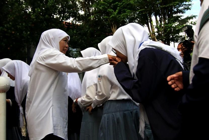 Gubernur Jawa Timur Khofifah Indar Parawansa (Kiri) menyalami siswa peserta Ujian Nasional Berbasis Komputer (UNBK) di SMKN 1 Giri, Banyuwangi, Jawa Timur, Senin (25/3/2019).