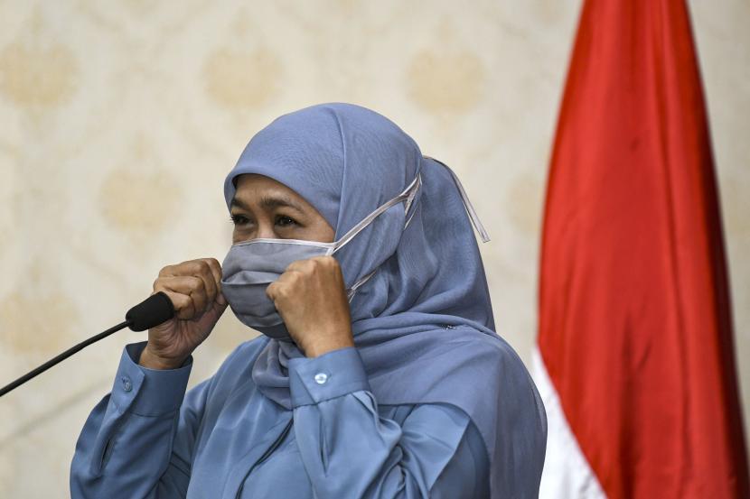 Gubernur Jawa Timur Khofifah Indar Parawansa merapikan masker di wajahnya disela-sela menyerahkan bantuan pada