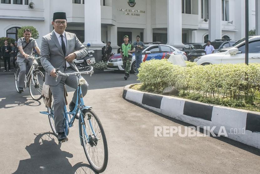 Gubernur Provinsi Jawa Barat terpilih, Ridwan Kamil menaiki sepeda usai diperkenalkan pada Rapat Paripurna Istimewa DPRD Jawa Barat di Gedung DPRD Jawa Barat, Bandung, Jawa Barat, Rabu (25/7).