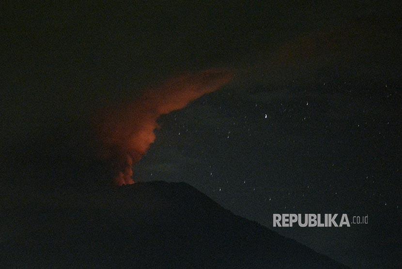 Gunung Agung mengeluarkannya asap berwarna kemerahan terlihat dari Desa Glumpang, Karangasem, Bali, Ahad (26/11) dini hari.