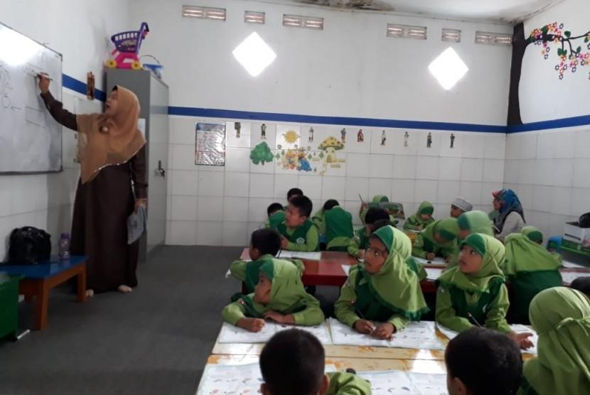 Guru di Rumah Pintar Astra Nurul Falah, Dati Daniati, sedang mengajar murid-muridnya. Rumah pintar ini berada di Mengger Girang, Kelurahan Pasirluyu,  Kecamatan Regol, Kota Bandung.