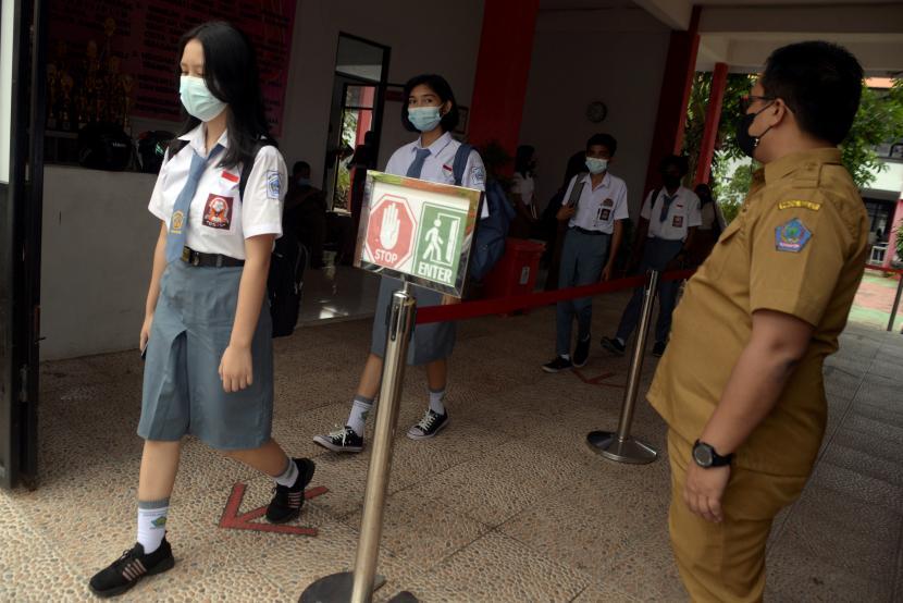 Guru mengawasi jalannya pelaksanaan protokol kesehatan di SMA Negeri 3, Manado, Sulawesi Utara, Selasa (21/9/2021). Pembelajaran Tatap Muka (PTM) secara terbatas mulai dilaksanakan di sejumlah SMA di Kota Manado dengan penerapan protokol kesehatan ketat, serta pembatasan jumlah siswa hingga 20 persen dari total keseluruhan siswa.