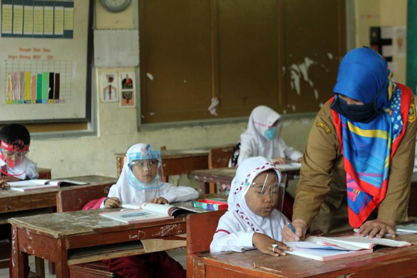 Guru menggunakan masker saat uji coba pembelajaran tatap muka (PTM) di SDN Tegalwaru 02, Ciampea, Kabupaten Bogor, Jawa Barat, Senin (15/3/2021).