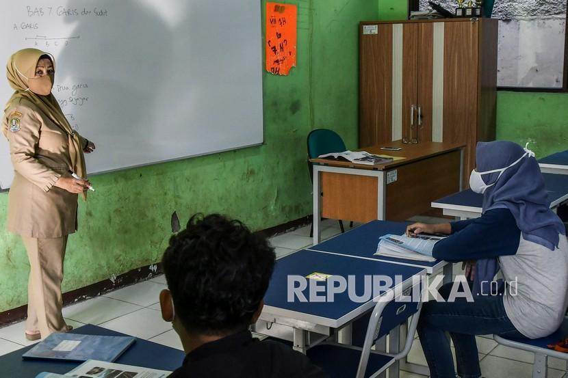 Guru menyampaikan materi pelajaran saat pembelajaran tatap muka di SMPN 2 Bekasi, Jawa Barat, Senin (22/3/2021). Dinas pendidikan Bekasi mengizinkan sekolah yang berada di wilayah zona hijau untuk menyelenggarakan pembelajaran tatap muka dengan menerapkan protokol kesehatan COVID-19 dan jumlah siswa masuk 50 persen.