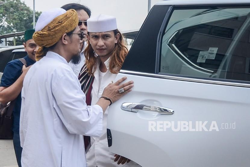 Habib Bahar bin Ali bin Smith (kanan) keluar dari kendaraannya untuk menjalani pemeriksaan perdana di Direktorat Kriminal Umum Polda Jawa Barat, Bandung, Jawa Barat, Selasa (18/12/2018).