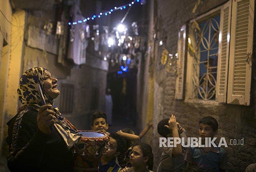 Hajjah Dalal (43) dikelilingi anak-anak  Dalal Abdel-Qader, saat membangunkan warga setempat bangun sahur di Distrik Ard Besari, Kairo, Mesir.