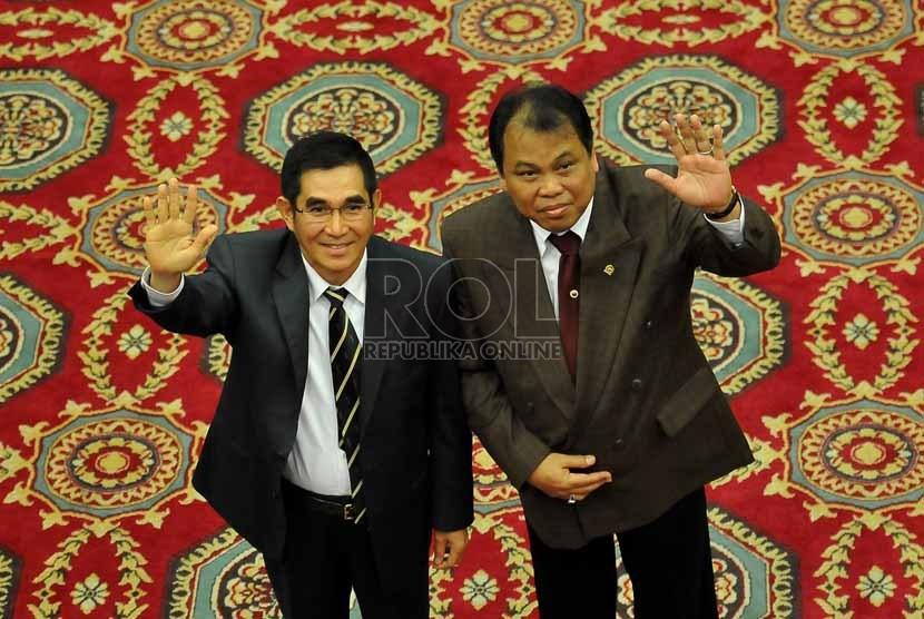 Hakim Konstitusi Hamdan Zoelva bersama Hakim Konstitusi Arief Hidayat melambaikan tangan kearah wartawan usai menjalani proses pemilihan ketua dan wakil ketua Mahkamah Konstitusi (MK) dengan sistem voting di Jakarta, Jumat (1/11).     (Republika/Prayogi)