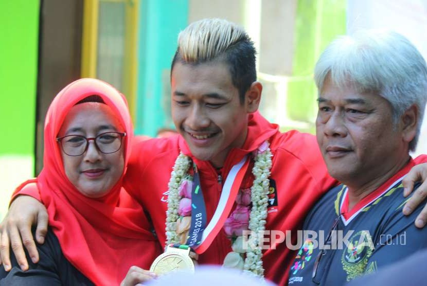Hanifan Yudani Kusuma, atlet pencak silat peraih medali emas di ajang Asian Games 2018 berfoto bersama kedua orang tuanya saat penyambutan oleh Ikatan Pencak Silat Indonesia (IPSI) Jawa Barat, di halaman GOR Tri Lomba Juang, Jalan Pajajaran, Kota Bandung, Senin (3/9).