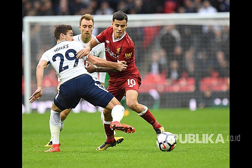 Pemain Tottenham Hotspur Harry Winks (kiri) berebut bola dengan pemain Liverpool Philippe Coutinho (kanan) pada pertandingan Liga Primer Inggris di Wembley, Inggris