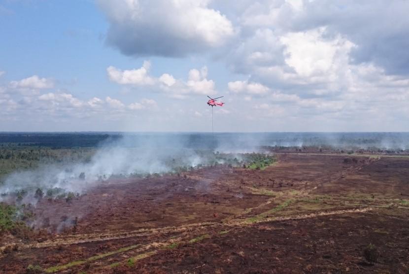 Heli jenis Superpuma Asia Pulp Paper (APP) Sinar Mas Forestry melakukan waterbombing di Teluk Meranti, Pelalawan, Riau.
