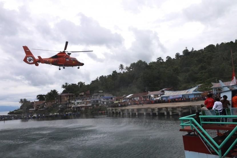 Helikopter Basarnas jenis Dauphin HR-3604 bersiap mendarat di Pelabuhan Tigaras, Danau Toba, saat melaksanakan pencarian korban tenggelamnya KM Sinar Bangun, di Simalungun, Sumatera Utara, Sabtu (23/6).