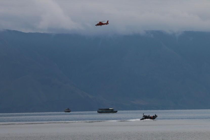 Helikopter Basarnas jenis Dauphin HR-3604 terbang di atas Danau Toba saat melaksanakan pencarian korban tenggelamnya KM Sinar Bangun, di Simalungun, Sumatera Utara, Sabtu (23/6).
