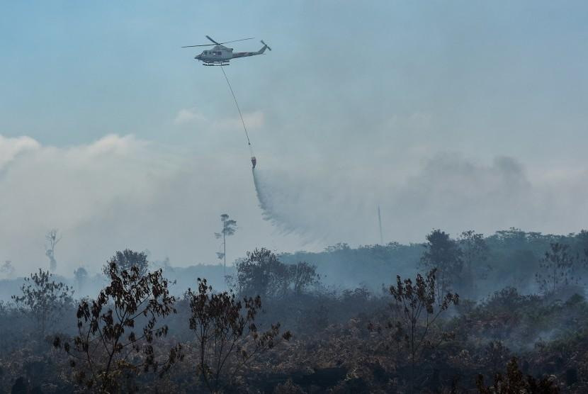 Pemadaman Karhutla: Helikopter Kementerian Lingkungan Hidup dan Kehutanan menjatuhkan air dari udara saat membantu proses pemadaman kebakaran hutan dan lahan di Pulau Rupat, Kabupaten Bengkalis, Riau, Kamis (28/2/2019).