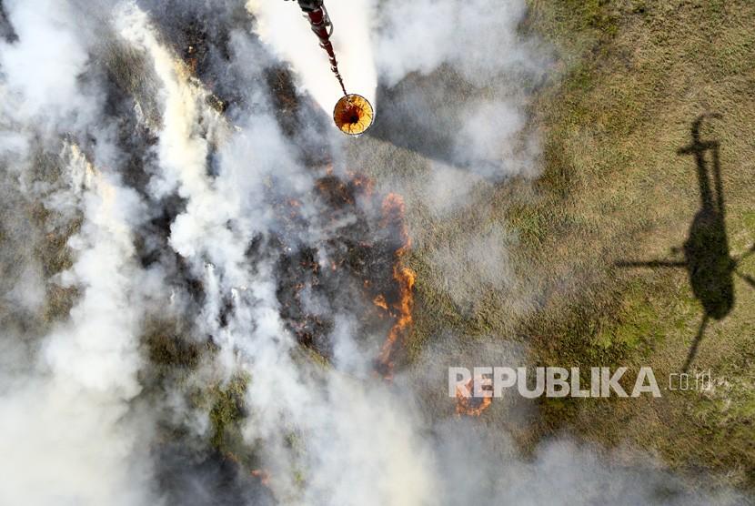 Helikopter MI-172 milik Badan Nasional Penanggulangan Bencana (BNPB) melakukan pemadaman kebakaran lahan dari udara water boombing di Tulung Selapan, Ogan Komering Ilir (OKI), Sumatera Selatan, Ahad (22/7).
