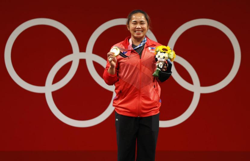 Hidilyn Diaz berpose dengan medali emas angkat besi putri 55 kg di Olimpiade Tokyo 2020.