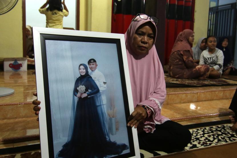 Ibu mertua Serda Pandu Yudha Kusuma awak KRI Nanggala 402 Yayak Dwi Ernawati (46) memegang foto pasangan Pandu dan Mega di rumahnya di Ketapang, Banyuwangi, Jawa Timur, Kamis (22/4/2021). Keluarga awak KRI Nanggala 402 yang hilang kontak saat menggelar latihan penembakan rudal di laut utara Bali pada Rabu (21/4) itu berkumpul menggelar doa bersama agar pencarian tim SAR diberikan kemudahan.