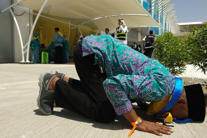 (Ilustrasi) Seorang jamaah haji bersujud syukur setibanya di Bandara Amir Muhammad bin Abdulaziz, Madinah, Sabtu (21/7).
