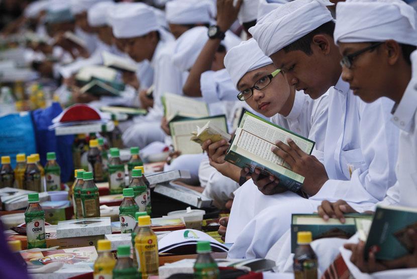 Ilustrasi Seorang anak membaca Al-quran saat menunggu waktu berbuka puasa bersama.