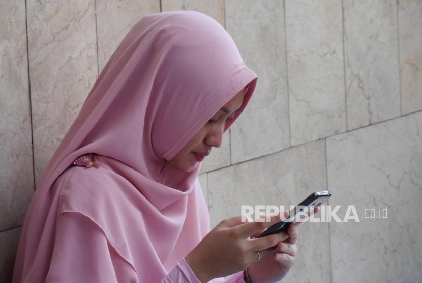 Ilustrasi Wanita berjilbab/wanita main gadget. (Republika/Darmawan)