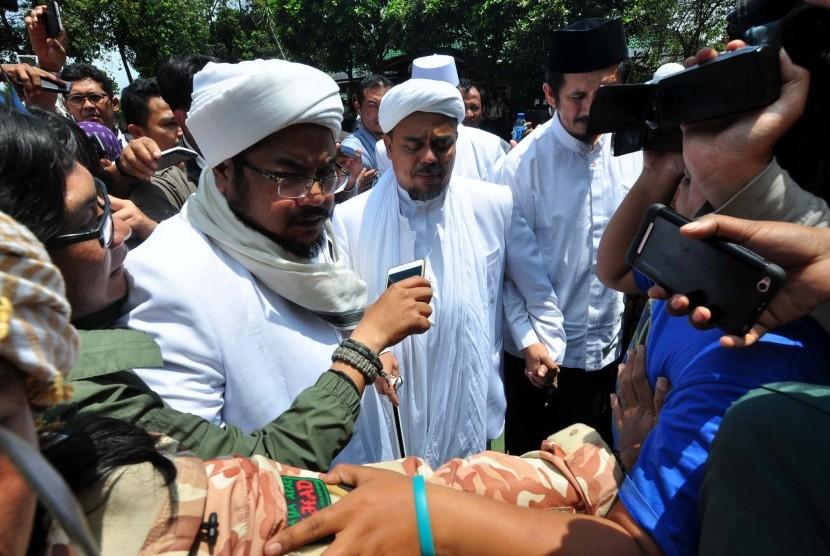 Imam Besar Front Pembela Islam (FPI) Habib Rizieq Syihab (tengah) menjawab pertanyaan wartawan saat menjalani pemeriksaan di Mapolda Jabar, Bandung, Jawa Barat, Senin (13/2).