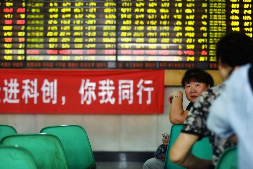 Investor bercengkrama di belakang layar yang menunjukkan pergerakan saham di Kota Hangzhou, Provinsi Zhejiang, China, Senin (22/7).