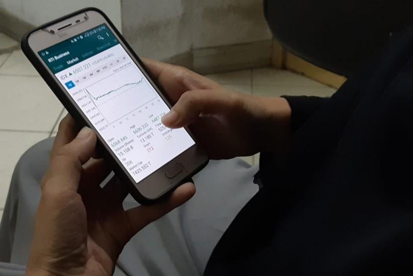 Investor memantau pergerakan Indeks Harga Saham Gabungan (IHSG) melalui ponsel pintar, Kamis (18/4).