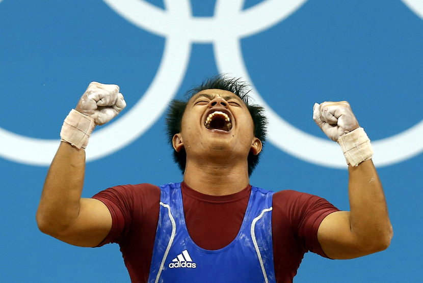 Jadi Setiadi bereaksi usai mengangkat beban saat berkompetisi pada cabang angkat besi Grup B kelas 56 kg di Olimpiade London di Excel, Ahad (29/7). (Dominic Ebenbichler/Reuters)