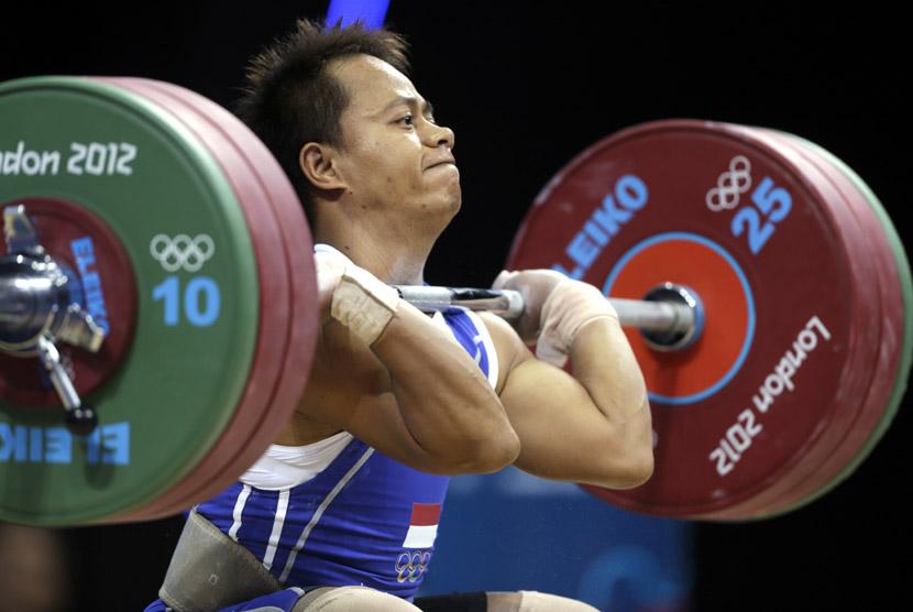 Jadi Setiadi berusaha mengangkat beban saat berkompetisi pada cabang angkat besi Grup B kelas 56 kg di Olimpiade London di Excel, Ahad (29/7). (Mike Groll/AP)