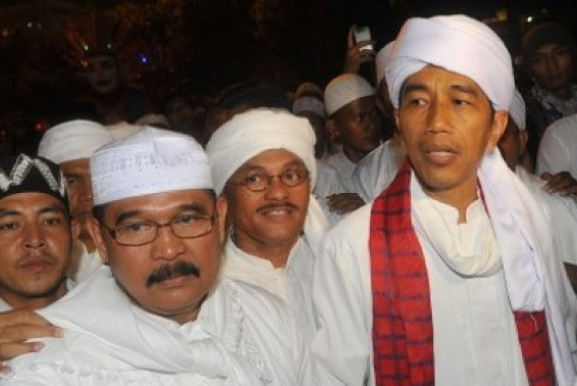 Jakarta governor Jokowi (right with red scarf) join the Jakarta Night Religious Festival parade on Monday, Oktober 14, 2013
